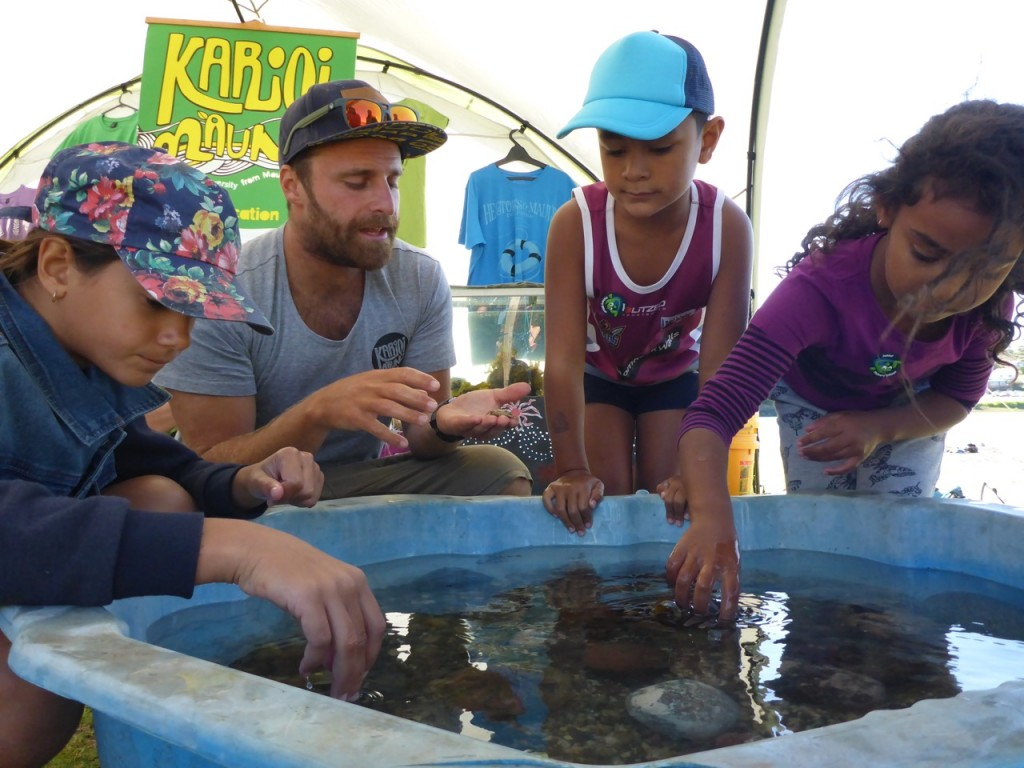 Nate with rocky shore touch tank at Maui Dolphin Day.